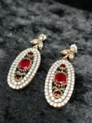 Silver red ruby colour stones and white stones drop earrings.