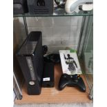 Xbox 360 slimline console with controller and game.
