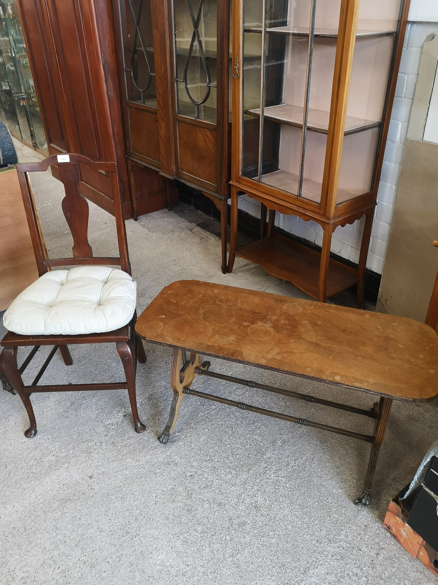 Vintage liar shaped end table with brass feet together with vintage chair.
