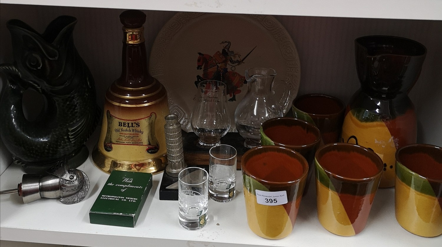 Shelf of collectables includes whisky jug and glass set on wooden plinth, gurgling jug etc.