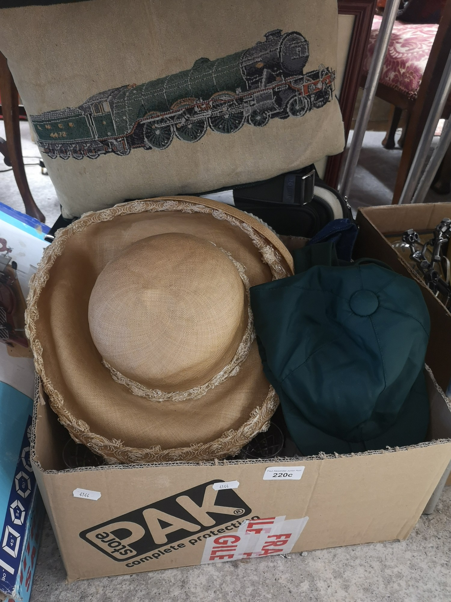 Box of event hats, crystal and train cushion.