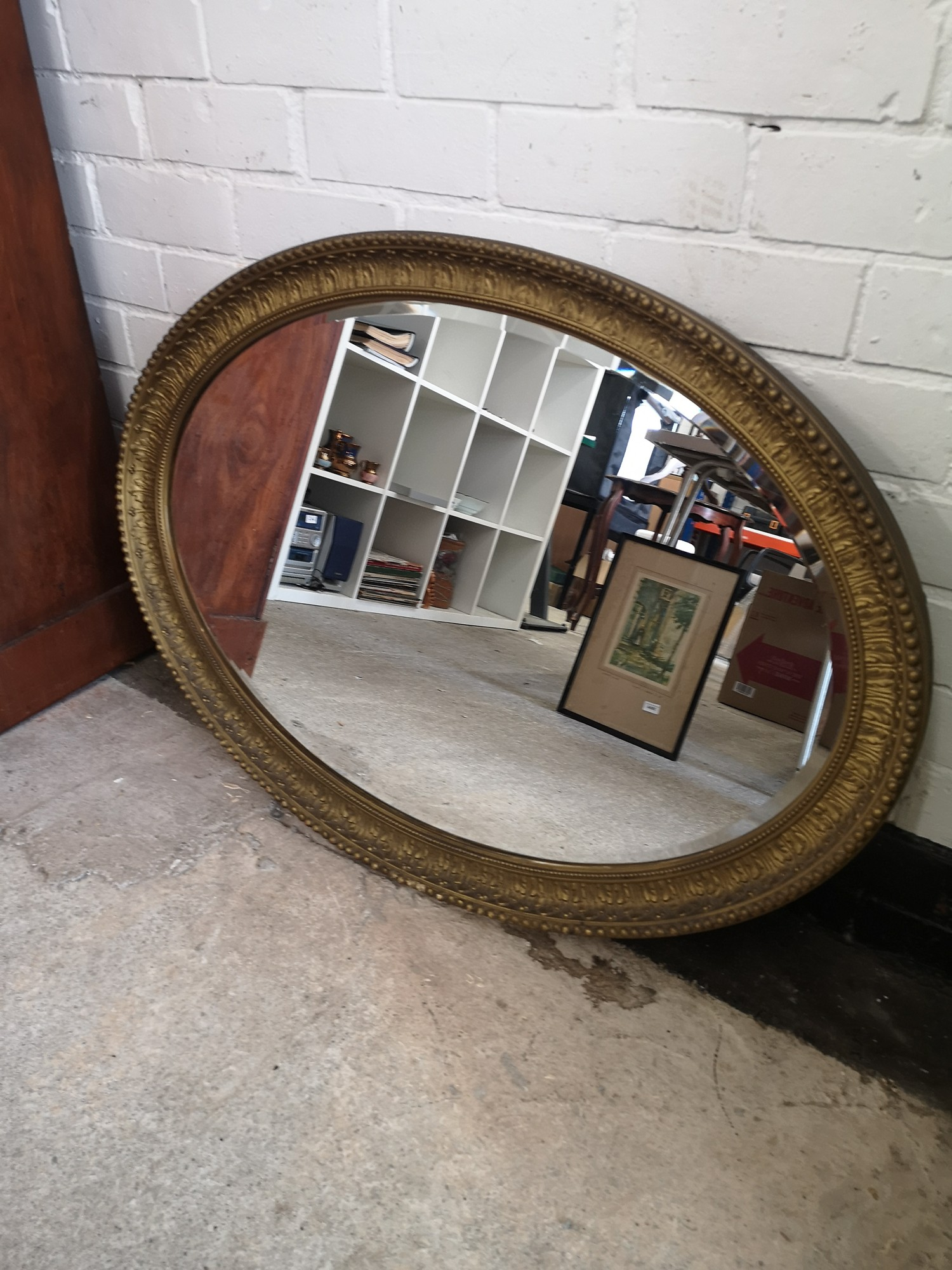 Large victorian oval mirror with carved design.