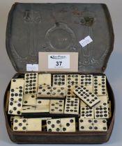 Art Nouveau metal tin, the interior revealing assorted bone dominoes. (B.P. 21% + VAT)