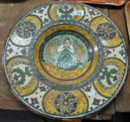 Large pottery charger decorated centrally with an angel and surrounded by floral decoration. (B.P.
