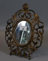 Gilt metal easel table mirror, having pierced scroll and foliate decoration, of oval form. (B.P. 21%