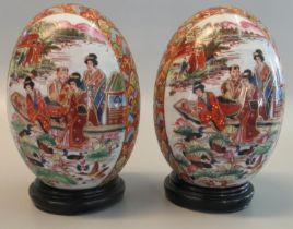 Pair of modern Chinese porcelain eggs decorated with reserved panels of figures in a boat on a lake.