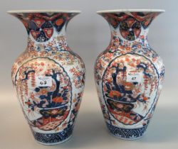 Pair of 19th Century Japanese Imari baluster shaped vases with flared necks, overall decorated in
