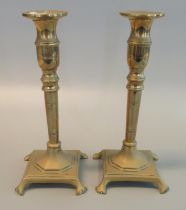 Pair of 19th Century brass candlesticks on square bases with paw feet. 24cm high approx. (2) (B.P.