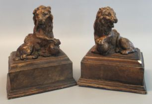 Pair of antiqued loaded plaster bookend type studies of male lions with front paw upon ball on