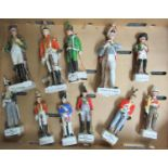 Box containing ceramic continental military figurines, some marked A with a crown to the bottom,
