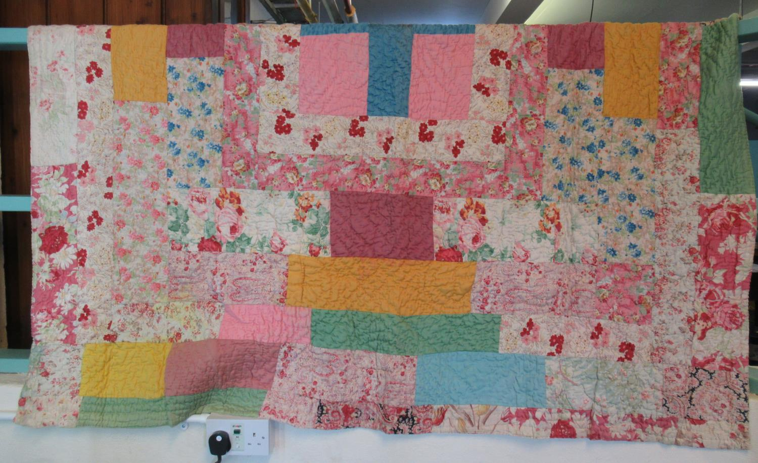 Colourful vintage patchwork cotton quilt with patches in various fabrics both floral and plain. (B.