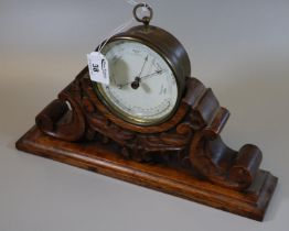 19th century brass drum shaped barometer with thermometer, unnamed, on a carved oak scrolled and