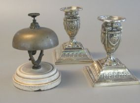 White metal reception bell on ceramic base, together with a pair of silver plated repousse decorated