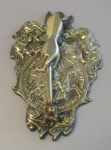 Heavy door knocker with relief brass back plate featuring mounted knight amid scroll work, with