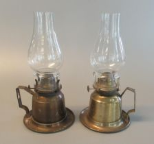 Near pair of similar brass single burner oil lamps with baluster clear glass chimneys and squared