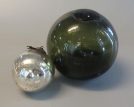Coloured glass fishing float with liquid contents, together with a small silvered watch or witch