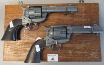 Pair of diecast metal replica colt revolvers on wooden display panel. (2) (B.P. 21% + VAT)