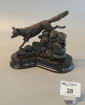 Modern patinated bronze sculpture of a fox leaping a stone wall on shaped wooden base. A