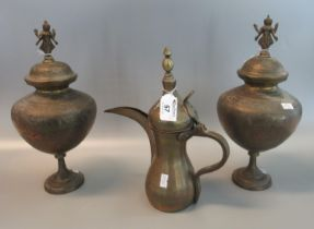 Pair of brass Indian style lidded pedestal urns with deity finials, together with a brass dallah. (
