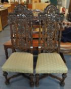 A pair of 20th Century heavily carved high back hall chairs with stuff over seats, standing on