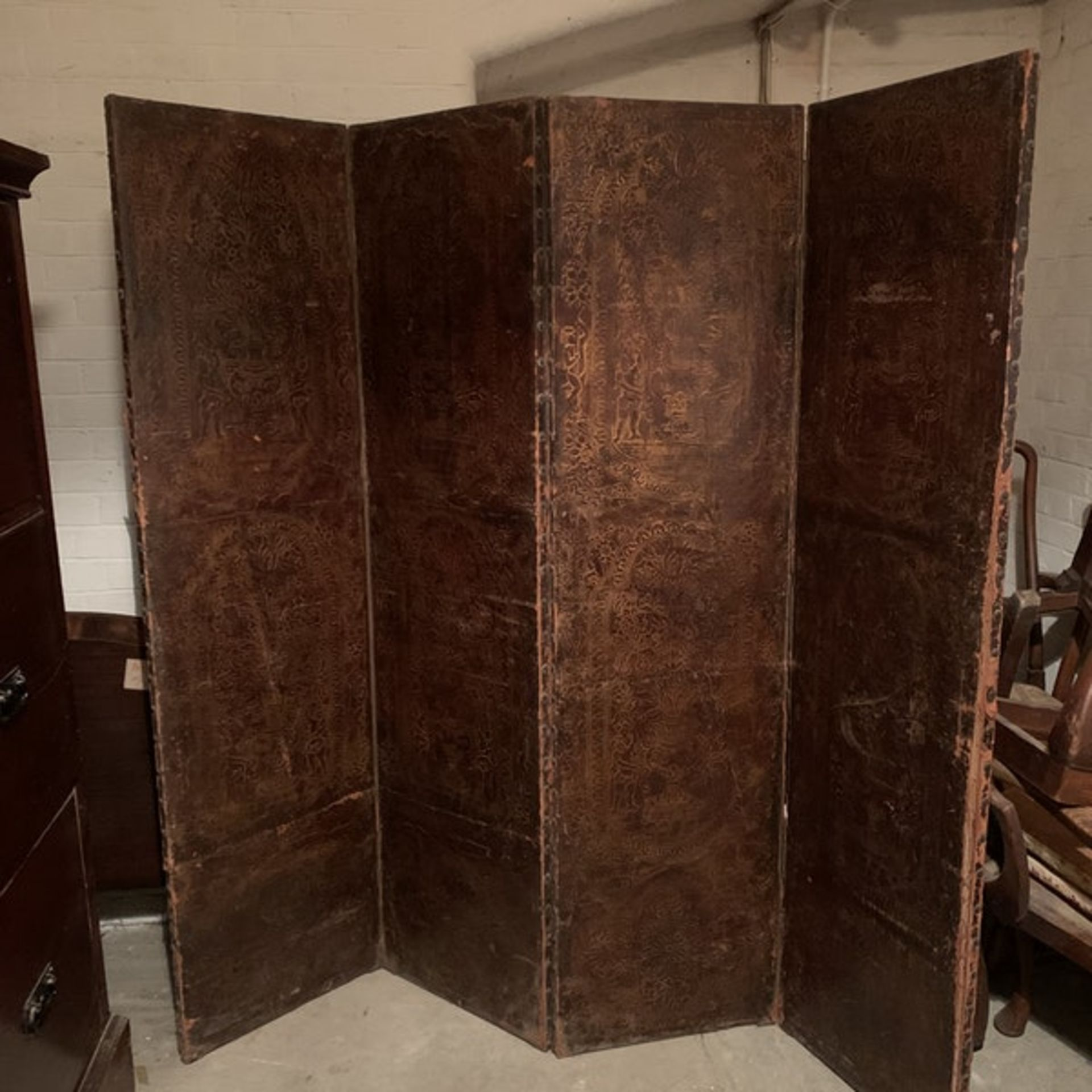 A 17th century style leather covered four fold screen, probably Spanish. Each fold covered in two
