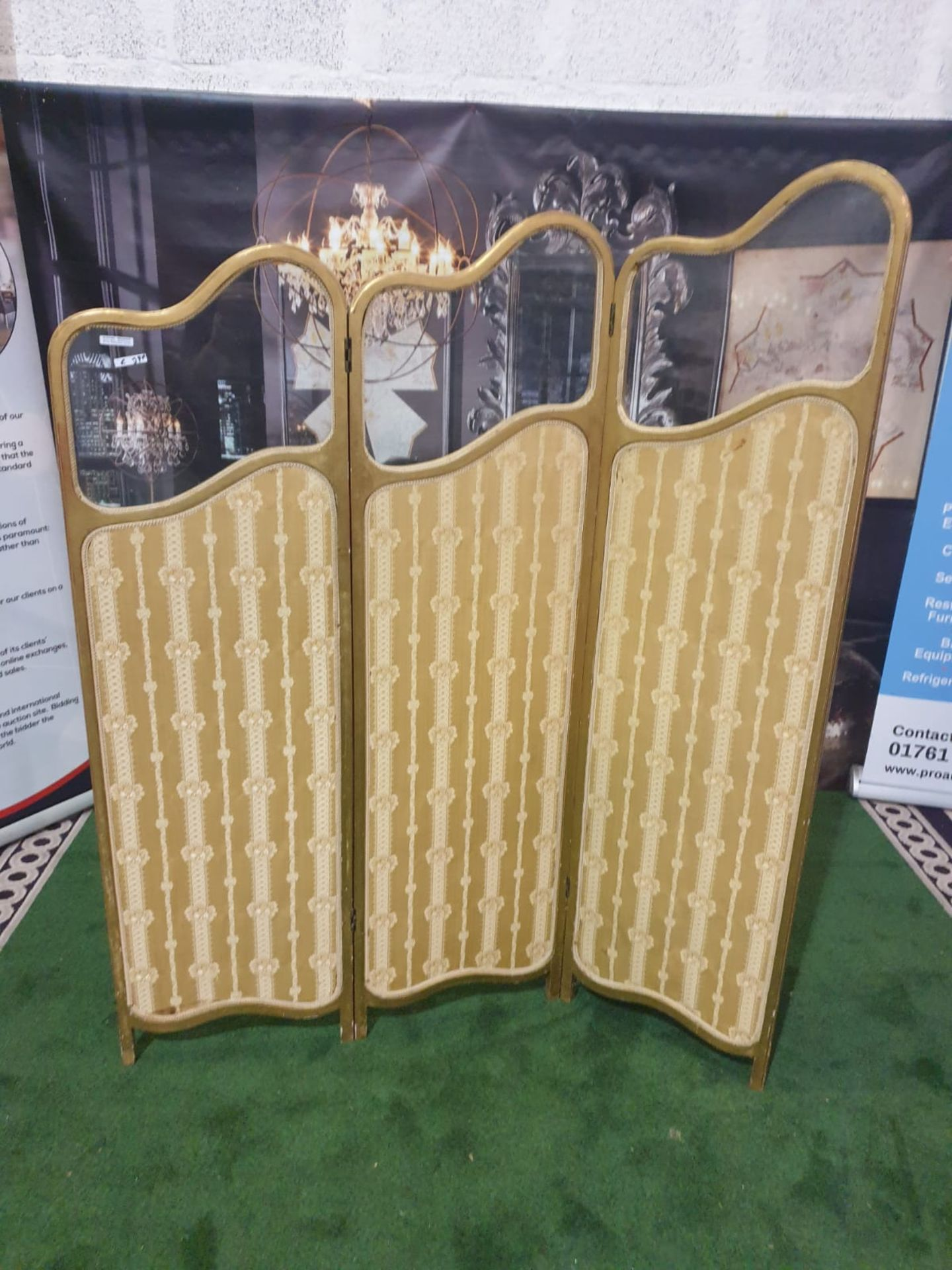 A giltwood and upholstered screen.The three graduated panels with glazed upper panels over damask-