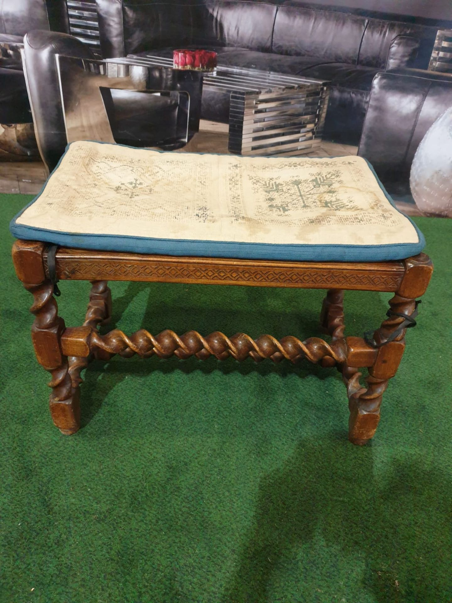 A walnut dressing stool. The oblong cushioned seat over a diaper-incised rail on twist-turned and