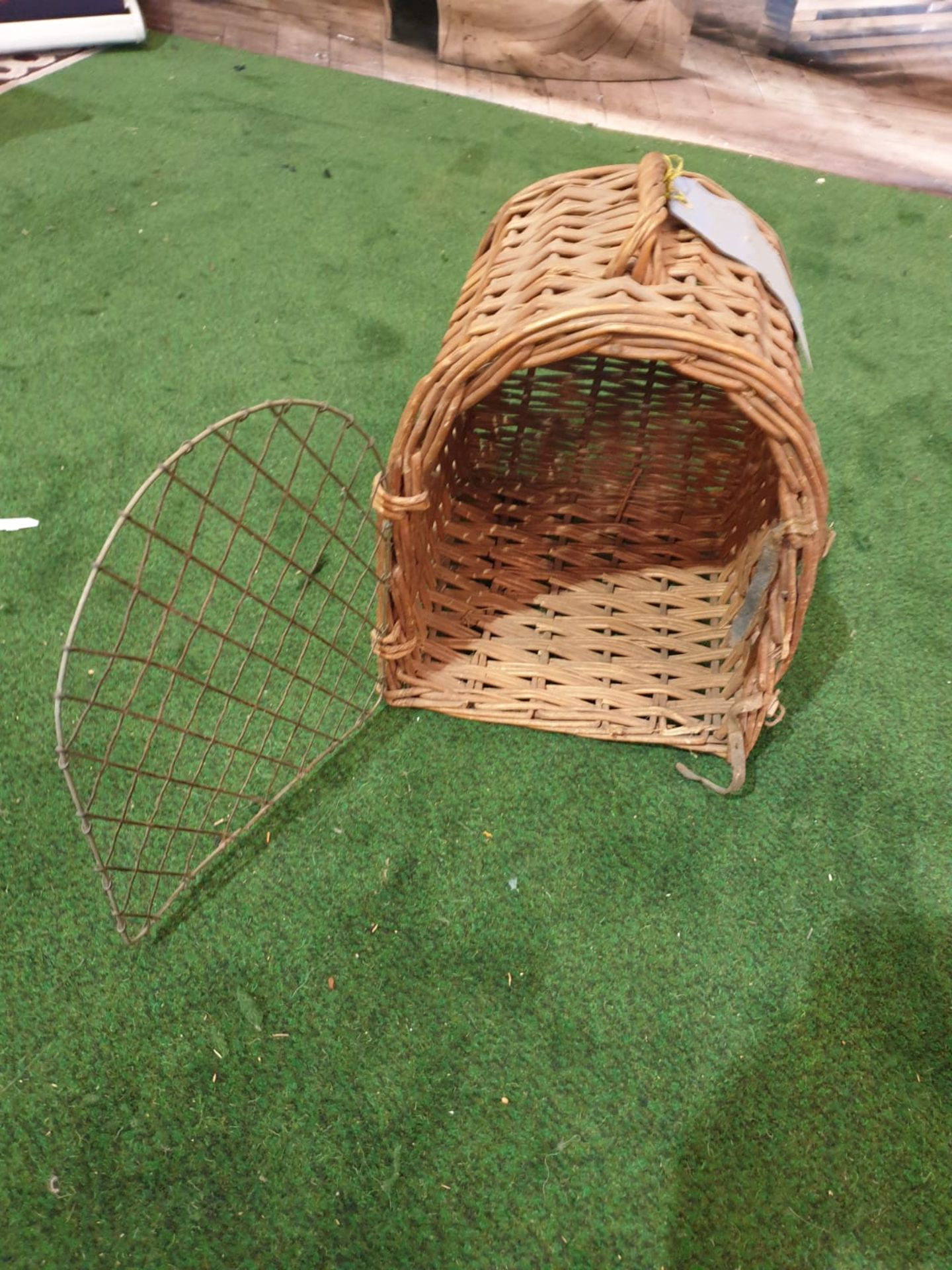"""A vintage wicker small pet carrier with paper tag stating """"Earl of Onslow"""""""