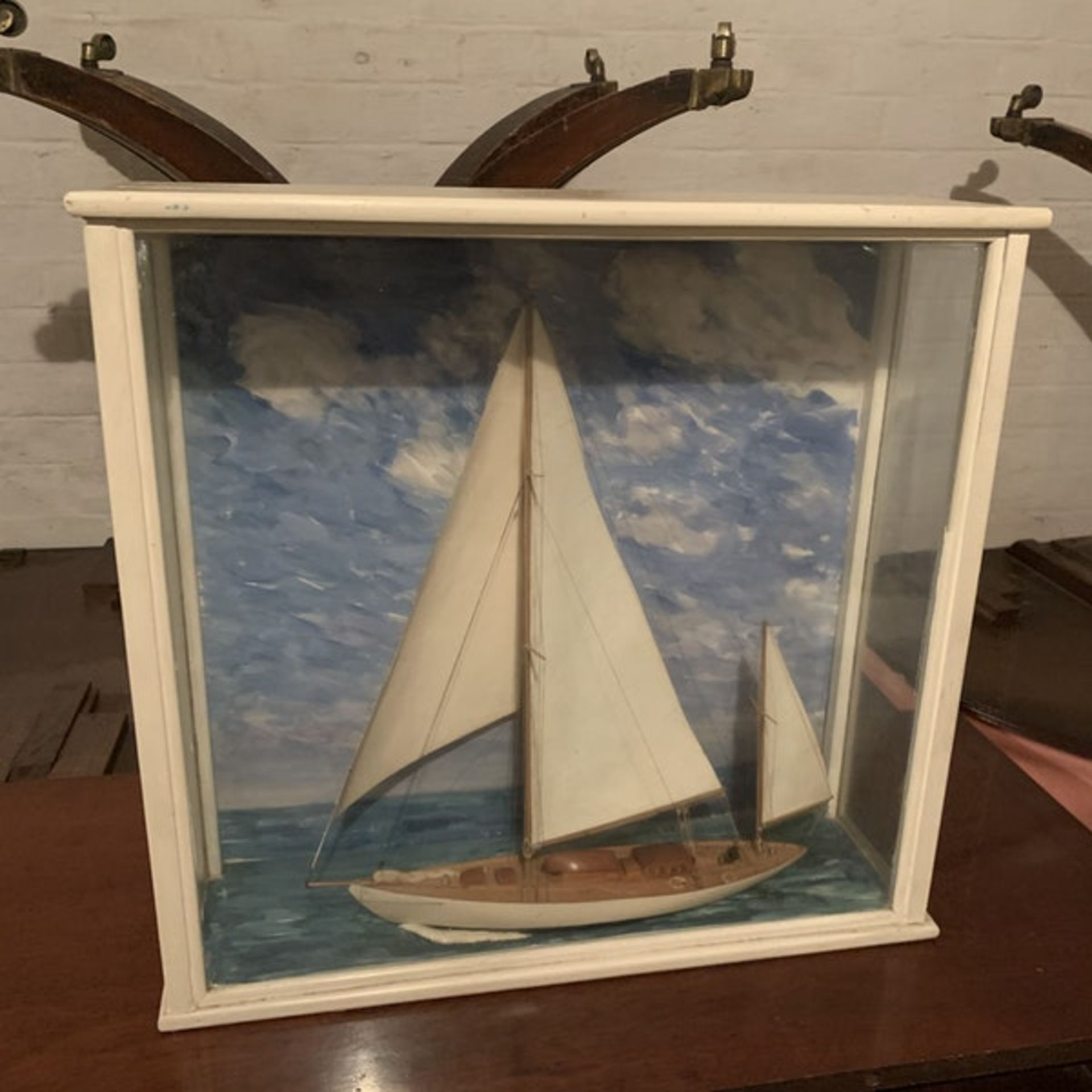 A scratch built model of a sailing yacht in a glass and painted wooden case. A scratch built model