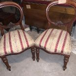 A pair of Victorian mahogany balloon back chairs. The moulded backs with carved aprons, the