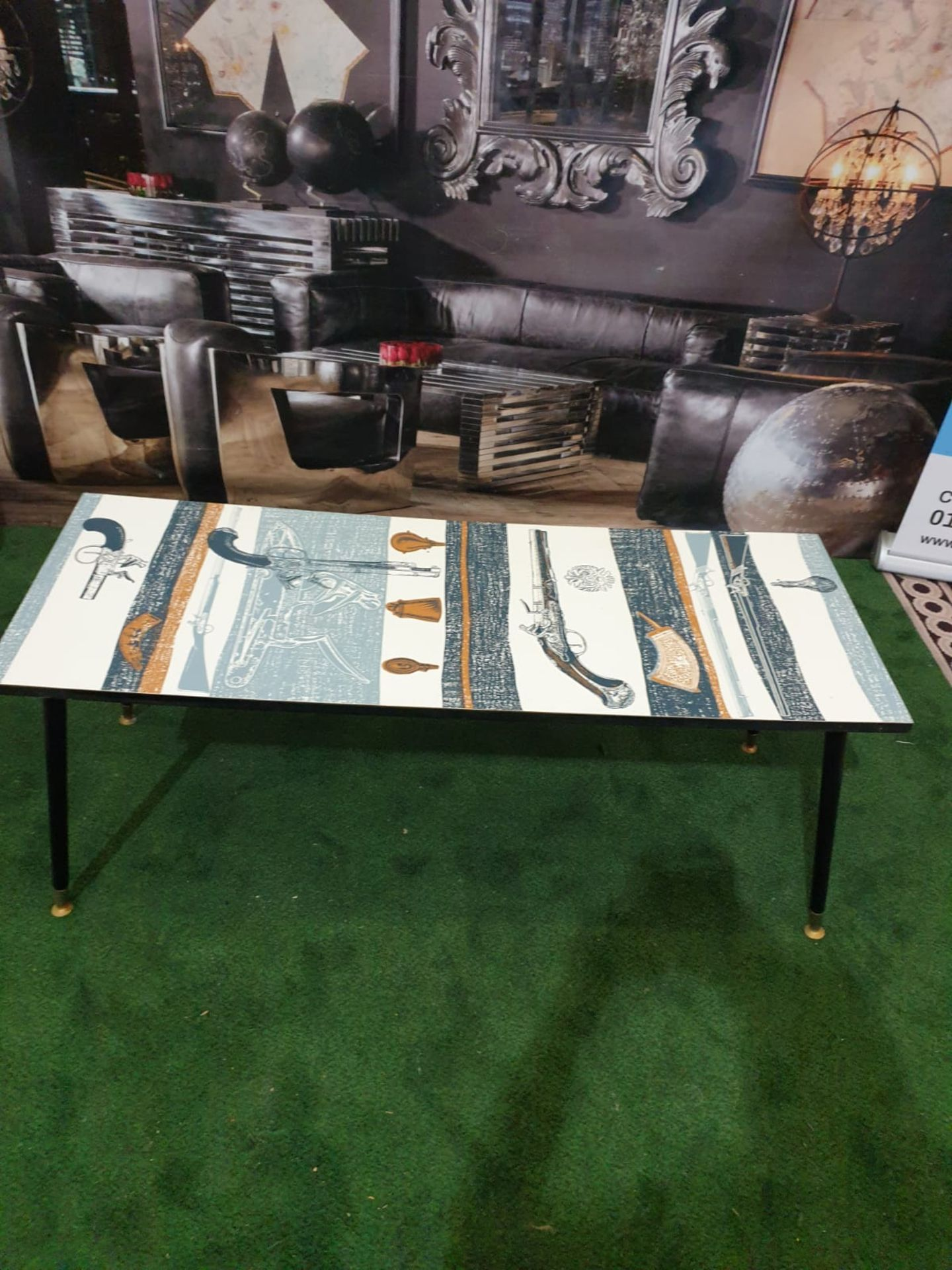 A 70's retro Coffee table with Pistol motifs laminated top on black legs 122 x 46 x 49cm