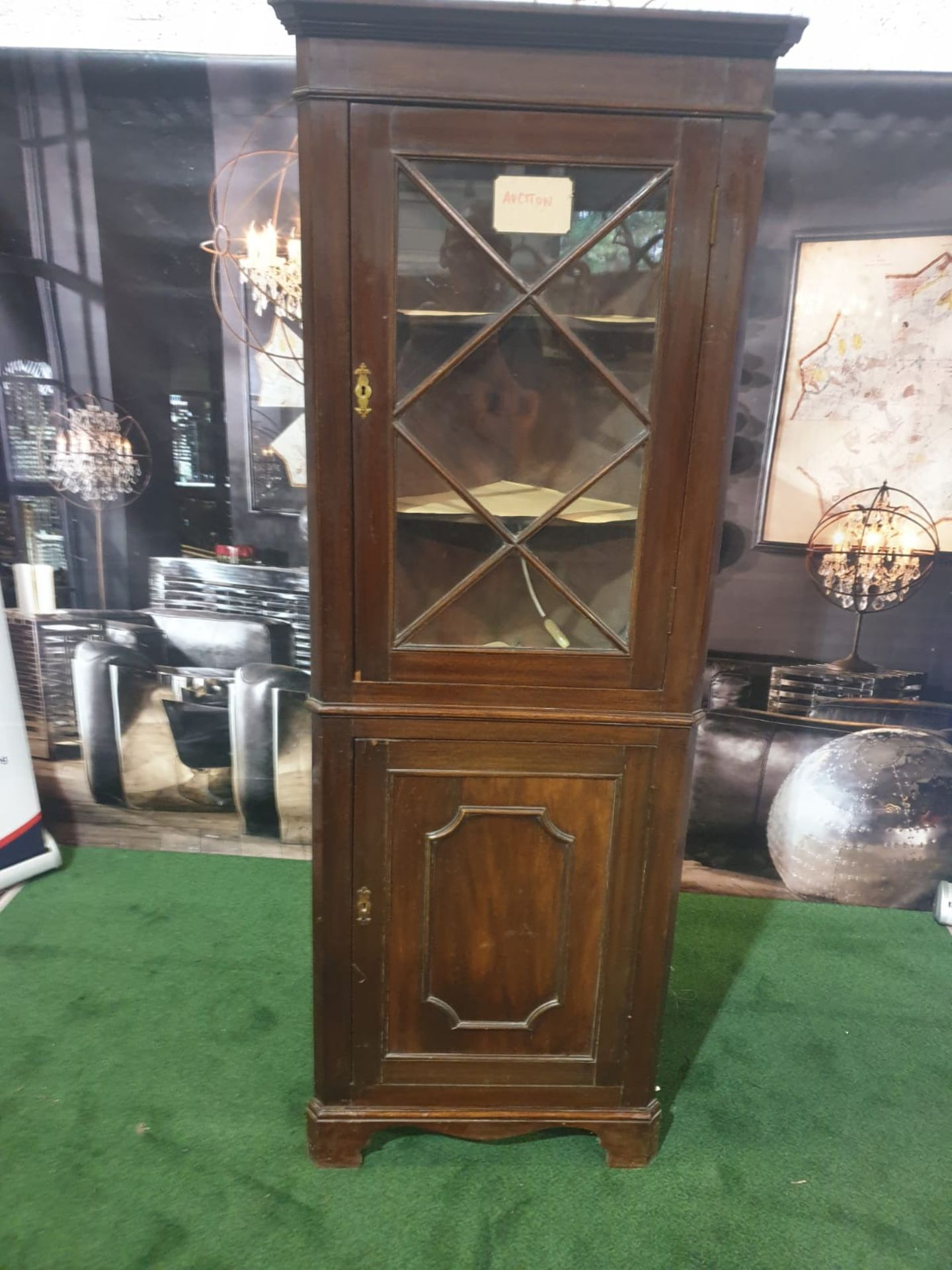 A mahogany standing corner cupboard in George III style. The moulded cornice above a single glazed