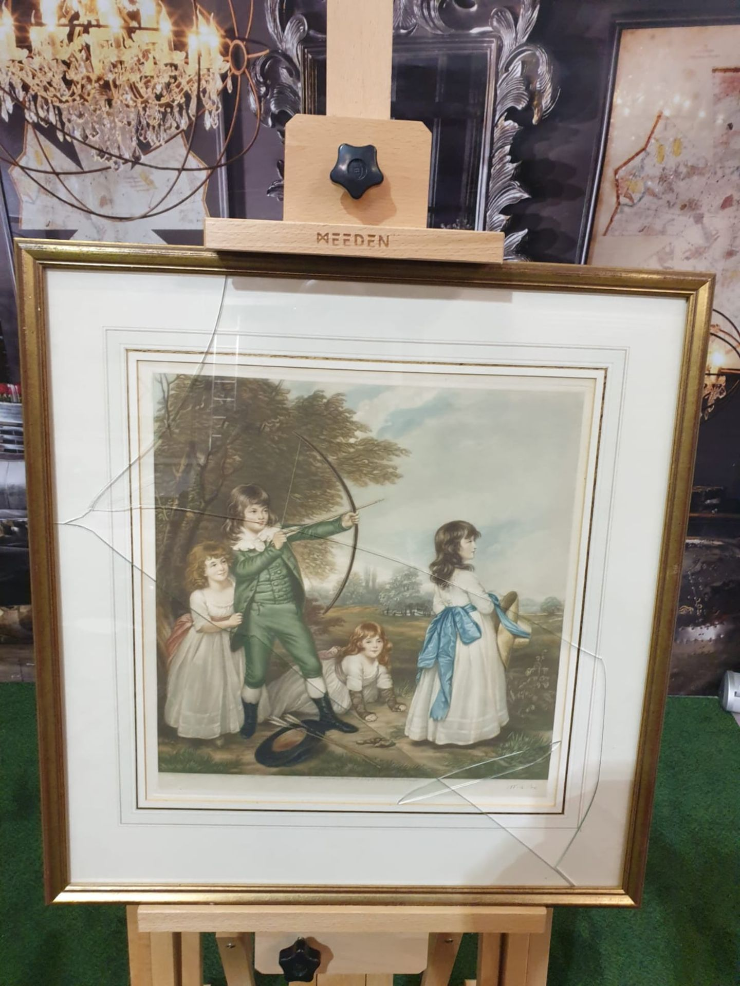 Framed coloured print of 4 Children playing, 1 child doing archery, hat and arrows on ground in