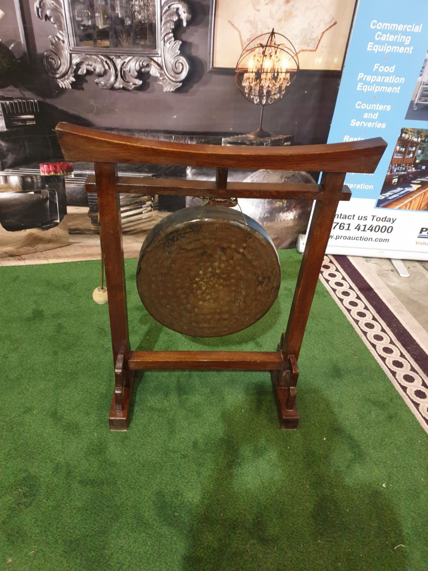 An Oriental brass gong on wooden stand An oriental, possibly Chinese circular hammered brass gong on