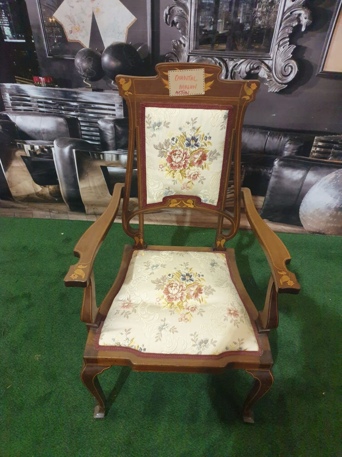A mahogany and marquetry armchair.The flower and leaf-inlaid shaped toprail above an oblong padded