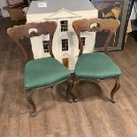 A pair of Victorian walnut chairs. The spoon shaped backs with moulded supports and a shaped and