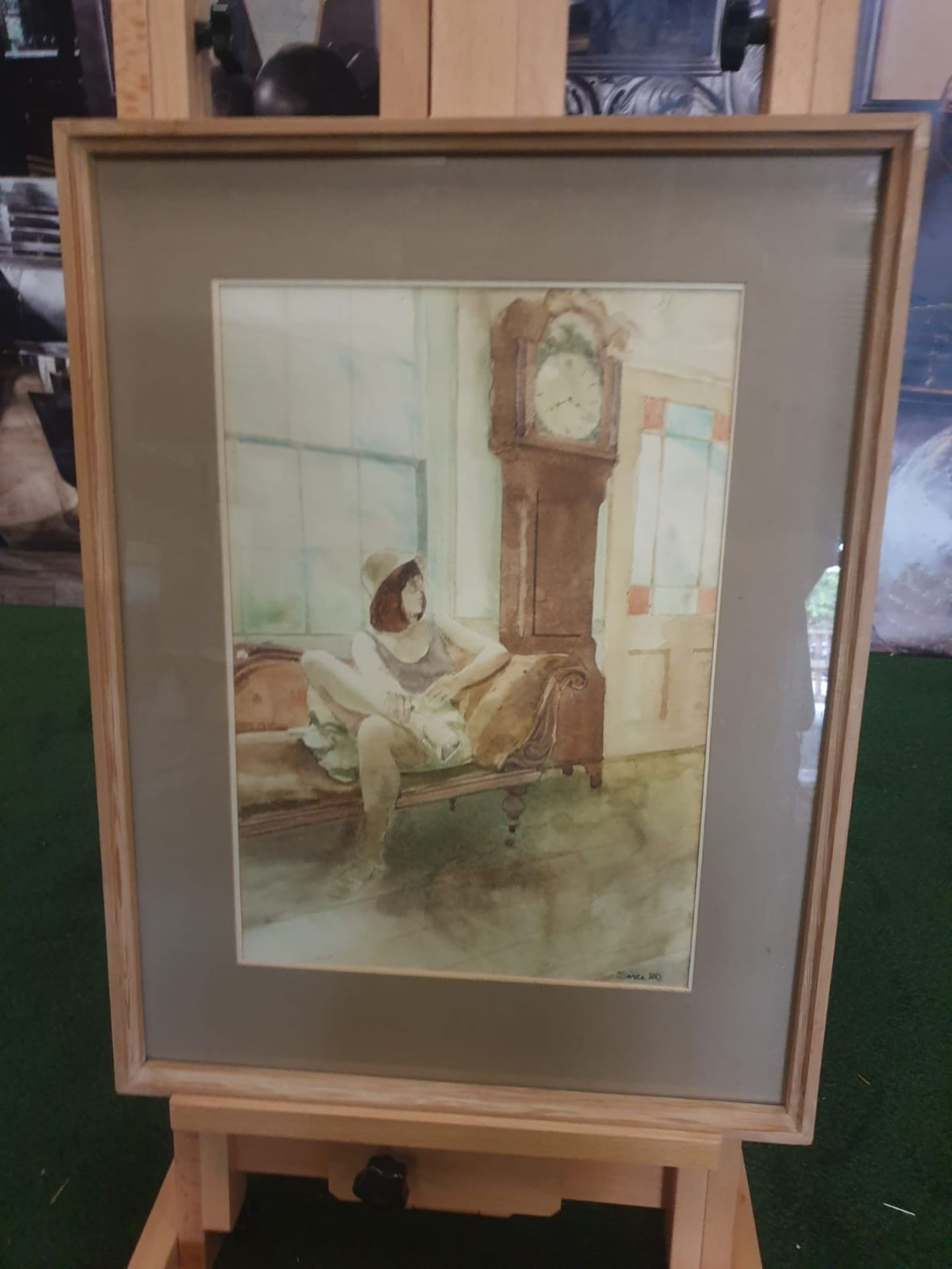 Framed watercolour Woman on chair by Grandfather clock singed and dated by Michael Smee '80