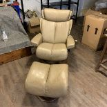 An Ekornes `Stressless` leather covered adjustable chair and stool, Norway. The pale caramel brown