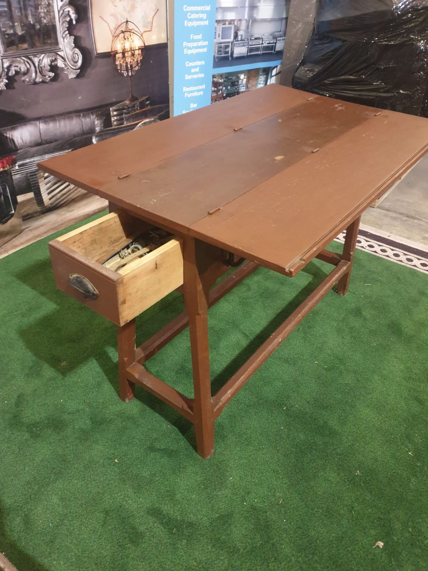 Stained wooden folding two-leaf table on tapering legs joined by a plain rail and having a drawer