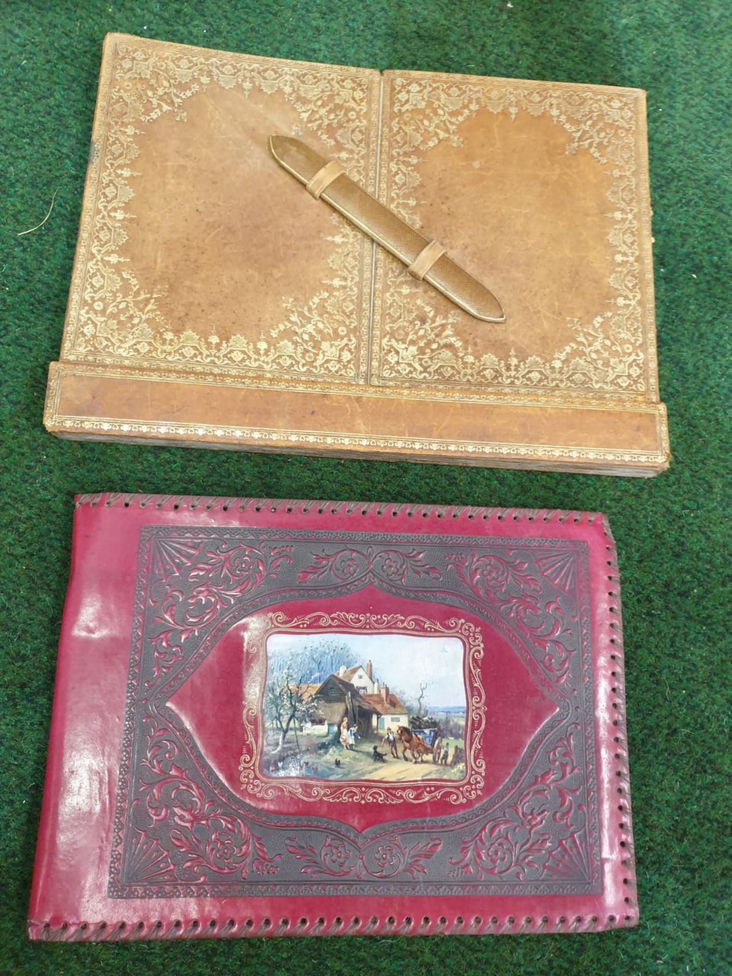 A vintage red leather with picture inset photo album and a tan light brown leather writing pad