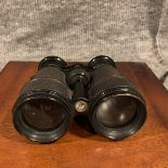 A Pair of vintage binoculars with black leather covered casing and black enamel trim, a compass is