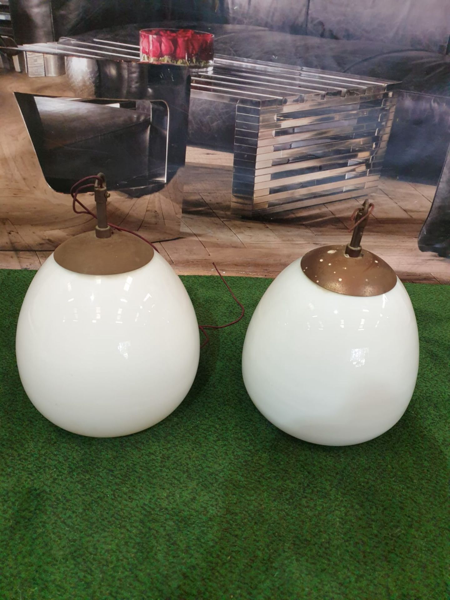 A pair of white glass and metal mounted pendant lights.Of ovoid form and with copper caps and