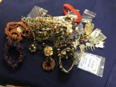A bag containing a mixed lot of beads, pendants, brooches, earrings etc. (a lot)