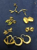 A mixed lot of 9ct gold and yellow metal earrings, including cameo rings, knot rings, hoop earrings,