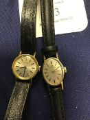 A lady's 9ct gold Omega Watch Company, oval wristwatch on leather band, together with a gold