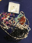 A bag containing a mixed lot of beads including freshwater pearls, mother of pearl, glass and