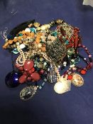 A bag containing a mixed lot of bead necklaces, pendants etc., including a millefiore style pendant,