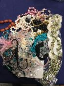 A bag containing a mixed lot of bead necklaces including glass, mother of pearl, polished stone,