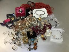 A large collection of costume jewellery including amber style earrings, turquoise ring, amber