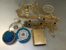 A collection of gilt chains, three compacts, a miniature clock, a miniature notebook, a bangle, a